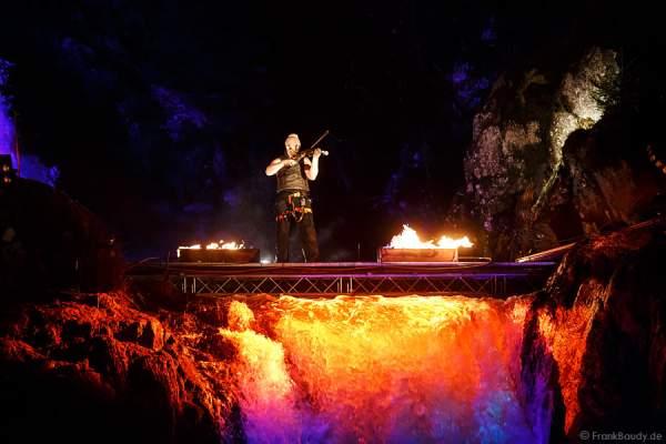 Hannes Schwarz mit Geige bei seiner Feuershow am Wasserfall des Triberger Weihnachtszauber