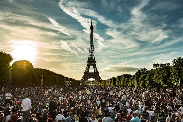 Besucher auf dem Champ de Mars warten am Abend auf das Konzert und das Feuerwerk auf dem Eiffelturm beim Nationalfeiertag am 14. Juli 2017 in Paris