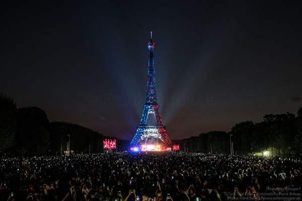 Beleuchteter Eiffelturm in Tricolor bei Nacht vor dem Feuerwerk beim Nationalfeiertag am 14. Juli 2018 in Paris