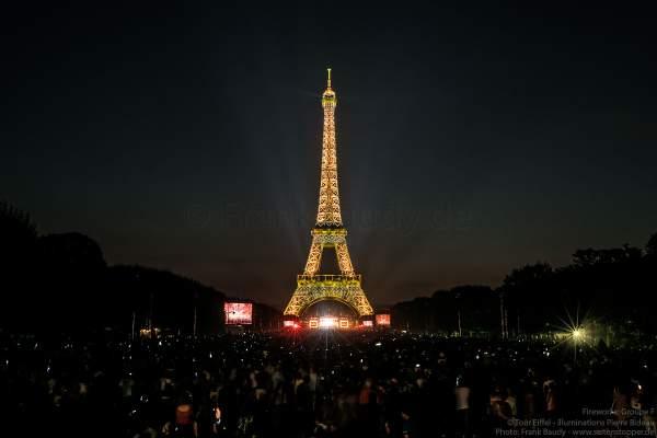 Besucher auf dem Champ de Mars warten am Abend auf das Konzert und das Feuerwerk auf dem Eiffelturm beim Nationalfeiertag am 14. Juli 2018 in Paris