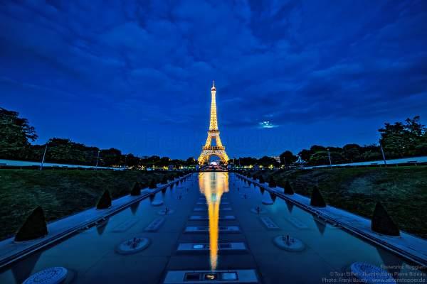 Illuminierter Eiffelturm bei Nacht spiegelt sich im Wasser vor dem großen Feuerwerk zum Nationalfeiertag am 14. Juli 2019 in Paris